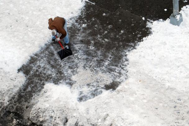 Man shoveling snow on driveway
